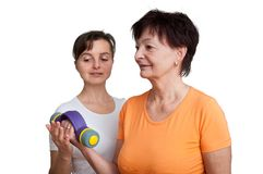 Coach assisting senior woman exercising Royalty Free Stock Image