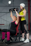 Coach assists to female in training with dumbbells in gym Stock Images