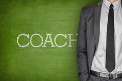 Coach on blackboard. With businessman in a suit on side Royalty Free Stock Image