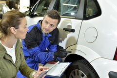 Coach-builder with insurer checking car reparations Royalty Free Stock Image