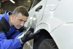 Coach-builder verifying car reparations Stock Image