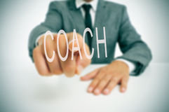 Coach. Businessman sitting in a desk pointing the word coach written in the foreground royalty free stock photo