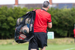 Coach carries footballs at match. Football coach Carries balls to training warm up Royalty Free Stock Photos