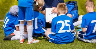 Coach Coaching Kids Soccer Team. Youth Football Team with Coach at the Soccer Stadium royalty free stock images