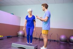 Coach controlling step exercise seniors. Coach controlling step exercise of seniors Stock Photography