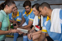 Coach discussing over digital tablet with volleyball players Stock Photography