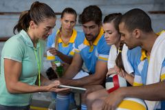 Coach discussing over tablet with volleyball players Royalty Free Stock Image
