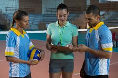 Coach discussing with volleyball players Stock Photo