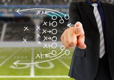 Coach drawing a tactics. Hand of a american football coach drawing a tactics of football game with white chalk on blackboard at arena stadium stock photos