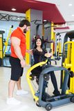 Sportswoman train with coaches help in gym. The coach is engaged with a women in the gym. The concept of a healthy lifestyle royalty free stock image