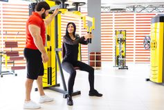 Sportswoman train with coaches help in gym. The coach is engaged with a women in the gym. The concept of a healthy lifestyle stock images