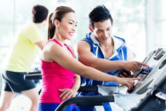 Coach evaluating performance of woman on treadmill. Male instructor evaluating fitness performance of young women on treadmill in gym Royalty Free Stock Images