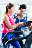 Coach evaluating performance of woman on treadmill. Male instructor evaluating fitness performance of young women on treadmill in gym Stock Photography