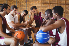 Coach explaining game plan to basketball players Stock Photography