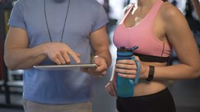 Coach explaining training schedule to female client, using tablet in the gym. Stock footage stock video footage
