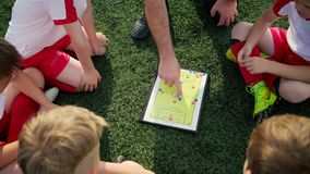 Coach explains game tactic moving coloured figures. Junior football team coach explains game tactic moving coloured figures on map close vertical view stock video