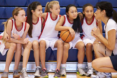 Coach Of Female High School Basketball Team Gives Team Talk. In Gym Looking At Each Other Stock Photography