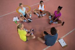 Coach and female player doing stretching exercise Royalty Free Stock Photography