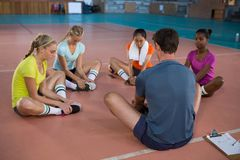 Coach and female player doing stretching exercise Stock Images