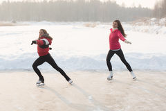 Coach of figure skating with apprentice practise at the frozen lake Stock Photography