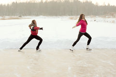 Coach of figure skating with apprentice practise at the frozen lake Royalty Free Stock Photo