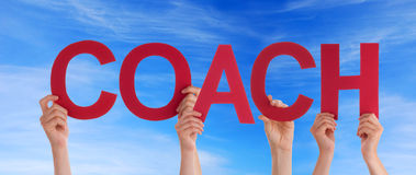 Coach in front of the Sky. Hands Holding the Word Coach in front of a blue Sky Stock Images