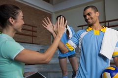 Coach giving high-five to male volleyball player. Coach giving high-five to happy male volleyball player on steps at court Stock Image