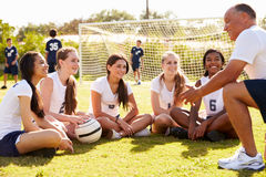 Coach Giving Team Talk To Female High School Soccer Team. With Teen Boys In Background Royalty Free Stock Photos