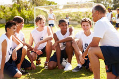 Coach Giving Team Talk To Male High School Soccer Team. Outside With People In Background Royalty Free Stock Photo