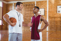 Coach guiding basketball player. While standing in court Royalty Free Stock Photography