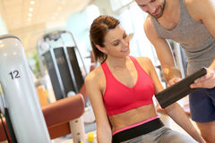 Coach guiding a fitness girl through a working out program. Fitness girl with coach setting up program Stock Image