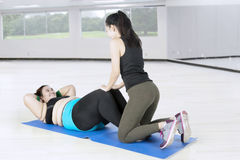 Coach helping fat woman for exercising Royalty Free Stock Image