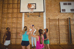 Coach helping high school team to score a goal while playing basketball. In the court Stock Image