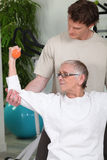 Coach helping senior lady. To do exercises Stock Images