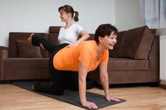 Coach helping senior woman exercising Stock Images