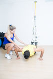 Coach helping with suspension training Stock Images
