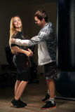 Coach helps the blonde girl in EMS suit to prepare for training. Coach helps the blonde girl in Electrical Muscular Stimulation suit to prepare for EMS training Royalty Free Stock Image