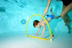 The coach helps the little boy swim underwater at the bottom of the pool through the Hoop. Shooting underwater from the bottom. Horizontal view Stock Image
