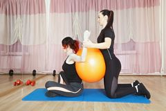 Safe stretching. Coach helps women to stretch body safely pressing ball on her back and holding her arms. Horizontal shot Stock Photo