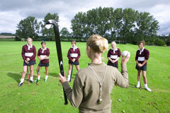 Coach holding field hockey stick and ball in front of team Royalty Free Stock Image