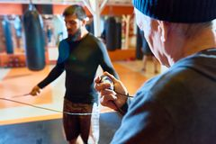 Coach Holding Stopwatch. Over shoulder view of unrecognizable coach holding stopwatch while timing young men jumping rope in fight club, copy space stock photos