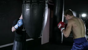 Coach holds the punching bag for his sportsman. Boxers fulfill in a couple of blows on the punching bag. One boxer holding punching bag and the other has an stock footage