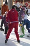 Coach at the ice rink teaches kids to skate Stock Photography