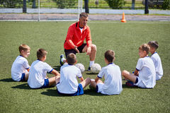 Coach Instructing Junior Football Team in Practice. Portrait of boys team sitting in front of coach on football field listening to pre game lecture Royalty Free Stock Image
