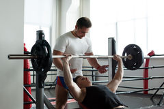 Coach insures athlete exercising with barbell Royalty Free Stock Photos