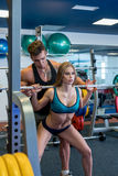 Coach insures girl while she squats with barbell Royalty Free Stock Photos