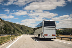 Coach, long haul bus, drives through Spain. A white coach, or long haul bus for tourists drives through the open roads of Spain, Europe on a summer day. There Royalty Free Stock Image