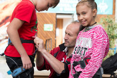 Coach makes safety check of harness of boy before climbing Royalty Free Stock Photography