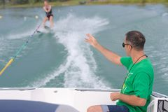 Coach making signs to female water ski student stock images