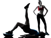 Coach man woman exercising abdominals with bosu Stock Photos